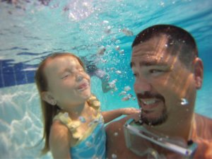 GoPro camera being used underwater to photograph L. Scott Harrell and daughter Maddie in the pool.